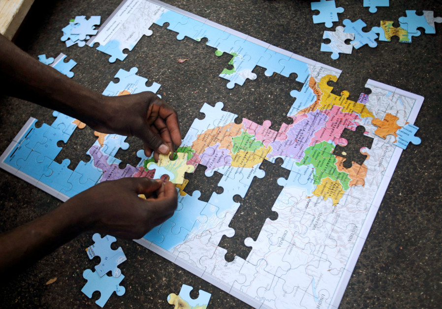 Migrants assemble a puzzle depicting Italy on a map, at a makeshift camp in Via Cupa