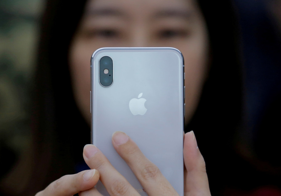 An attendee uses a new iPhone X during a presentation for the media in Beijing, China, 2017.