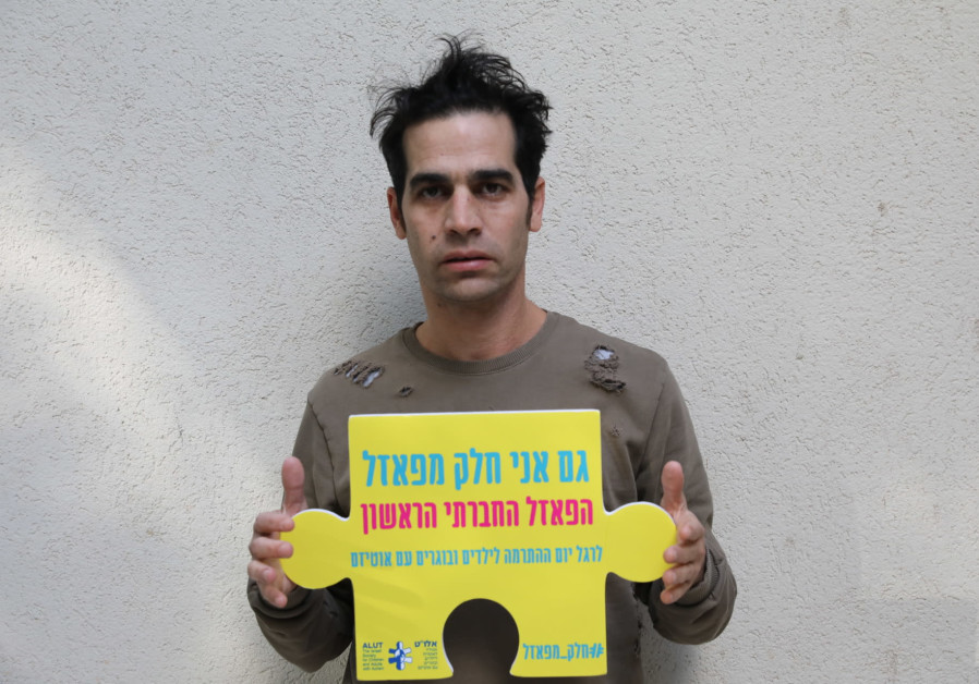"Musician Aviv Geffen holds a ""piece of the puzzle"" as part of ALUT's project (Ezra Levy)"