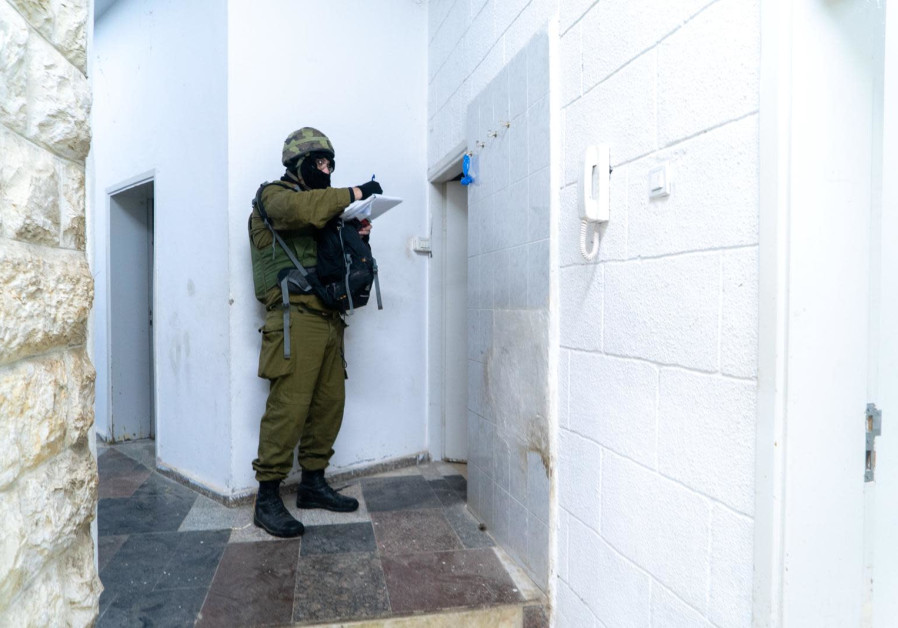 An IDF soldier maps out the home of the Barghouti brother terrorists