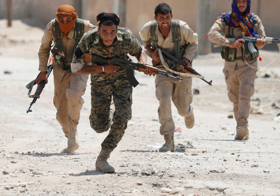 Kurdish fighters from the People's Protection Units (YPG) run across a street in Raqqa, Syria, July