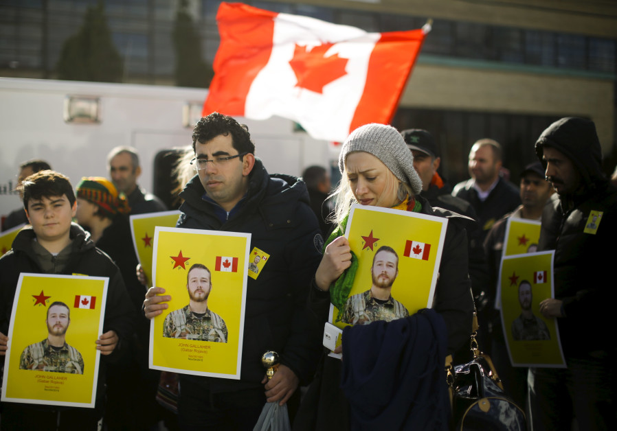 Mourners hold photos of John Gallagher, a Canadian volunteer fighter