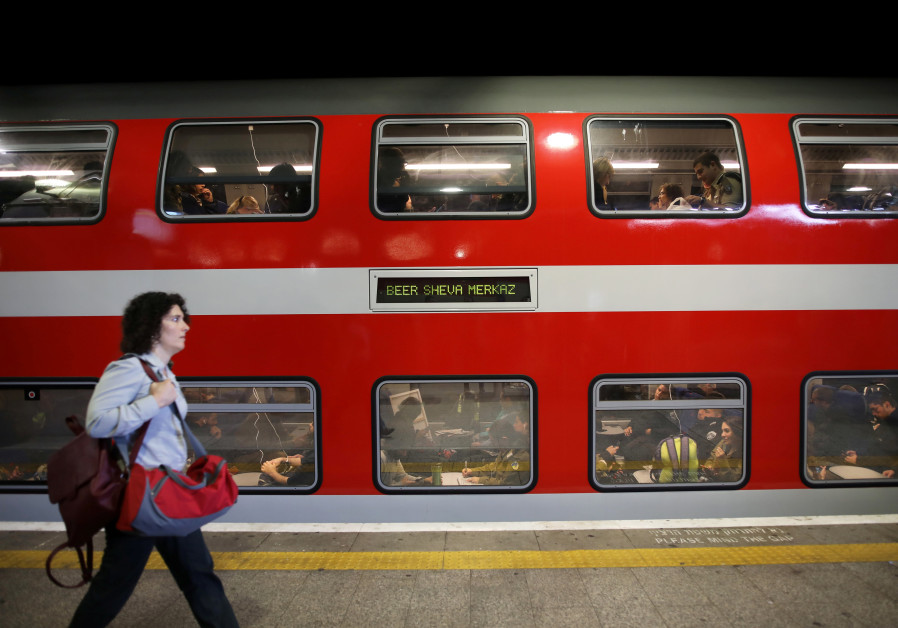 A woman walks on a platform in front of a train as passengers are seen through the carriage windows