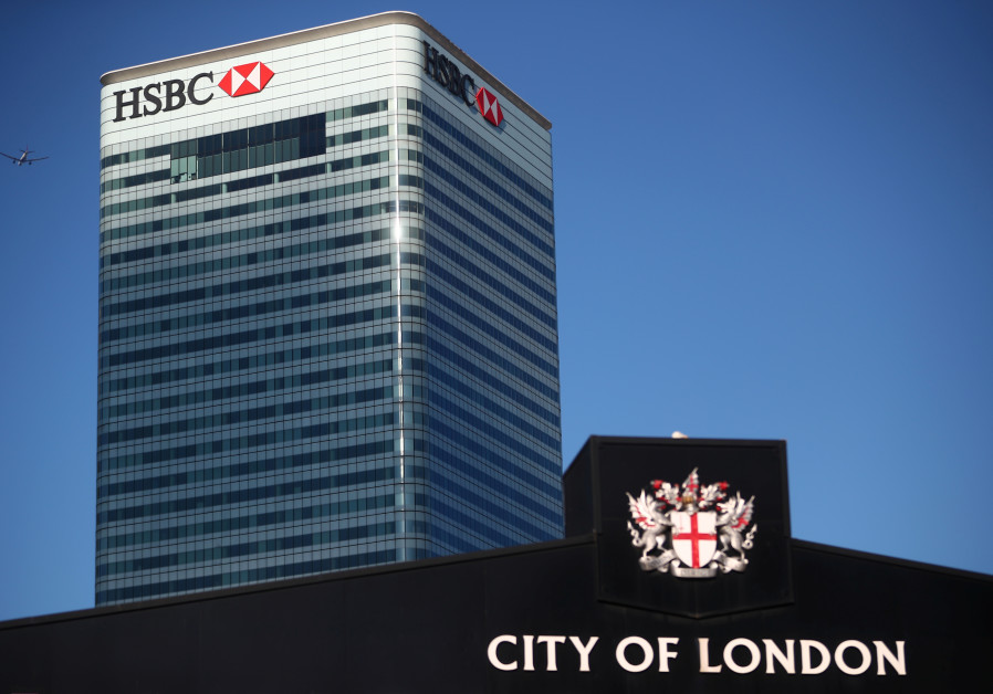 Barclays' building in Canary Wharf is seen behind a City of London sign outside Billingsgate Market