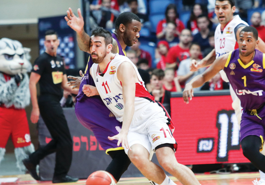 Hapoel Jerusalem's Bar Timor drives to the basket against the Hapoel Holon defense during the Reds'