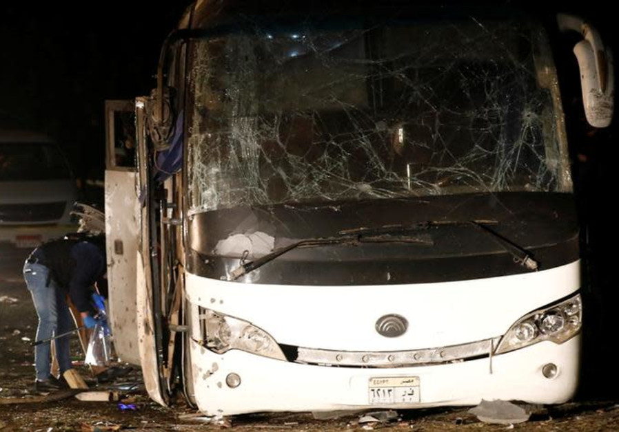 Police officers inspect a scene of a bus blast in Giza, Egypt, December 28, 2018.