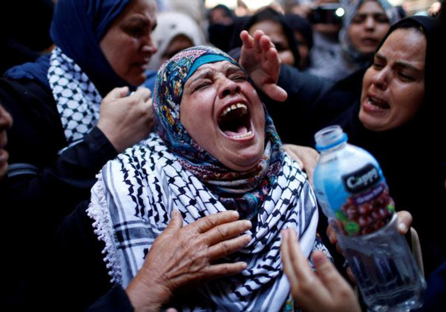 A relative mourns during the funeral of Palestinian nurse Razan Al-Najar.
