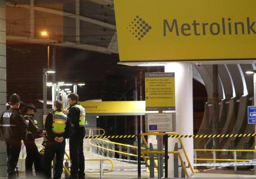 Police officers stand at the end of a tram platform following a stabbing at Victoria Station