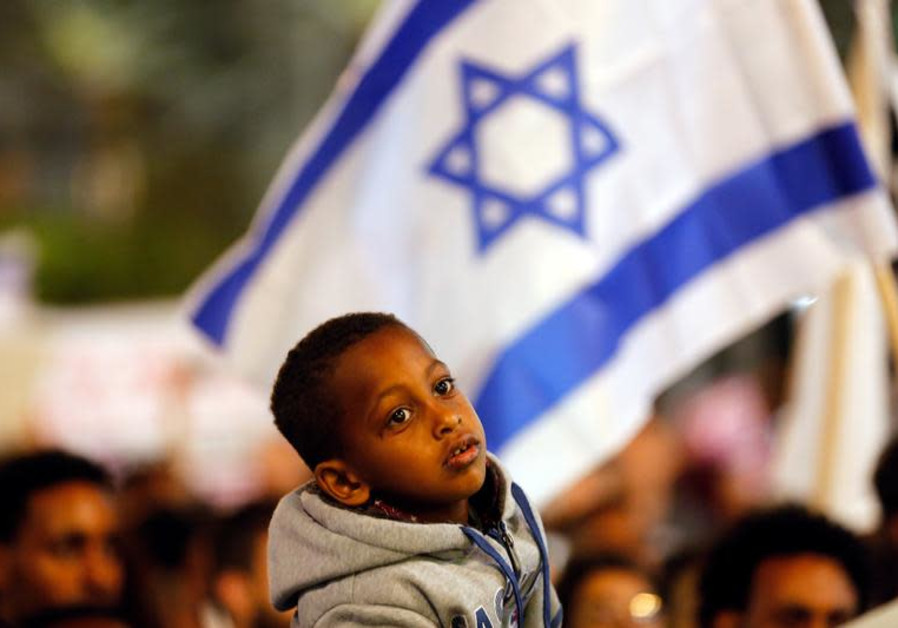 A boy takes part in a protest against the Israeli government's plan to deport African migrants, in T