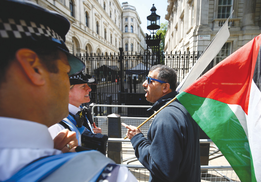 POLICE OFFICERS speak to a demonstrator holding a Palestinian flag in London ahead of Prime Minister