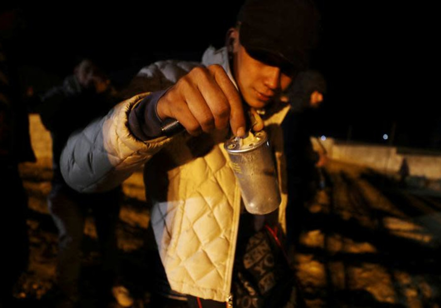 A migrant, holds a tear gas canister after CBP officials threw it to the Mexican side of the fence.