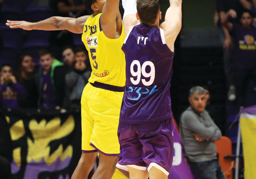 HAPOEL HOLON forward Darion Atkins (left) blocks a shot by Ironi Nahariya's Yiftach Ziv during first