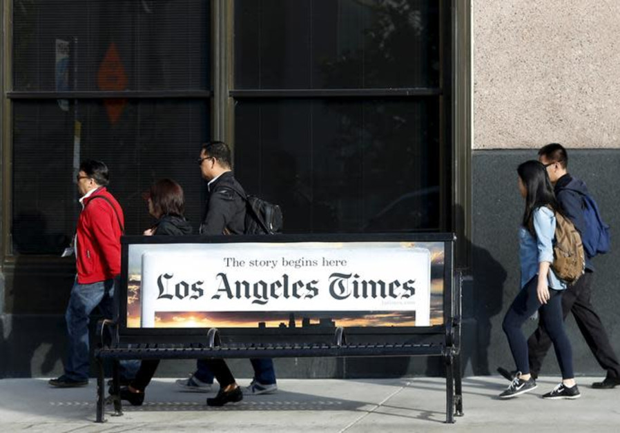 People walk past the building of Los Angeles Times newspaper
