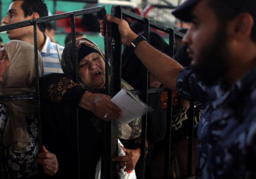 A woman gestures as she waits to travel into Egypt through Rafah border crossing.