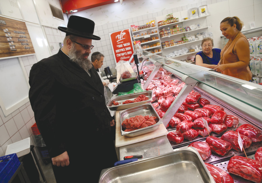 KOSHER INSPECTOR Aaron Wulkan examines meat to ensure that the food is stored and prepared.