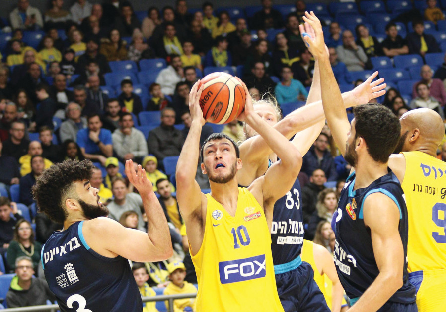 MACCABI TEL AVIV'S Nimrod Levi drives to the basket against the Hapoel Eilat defense during Maccabi