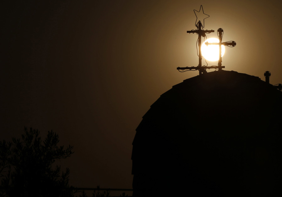 A Roman Catholic church cross is seen as the sun sets before Christians take part in a candlelight m