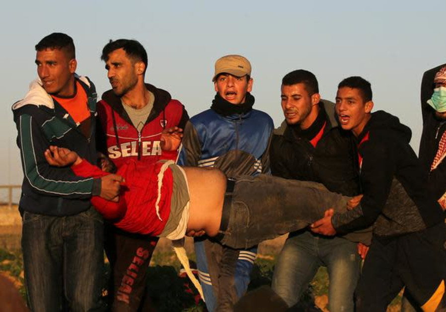 Palestinians evacuate a demonstrator during a protest at the Israel-Gaza border fence