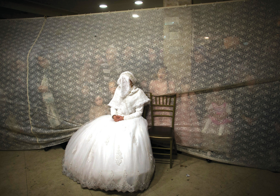 A JEWISH bride waits for her groom during a traditional wedding ceremony in Jerusalem