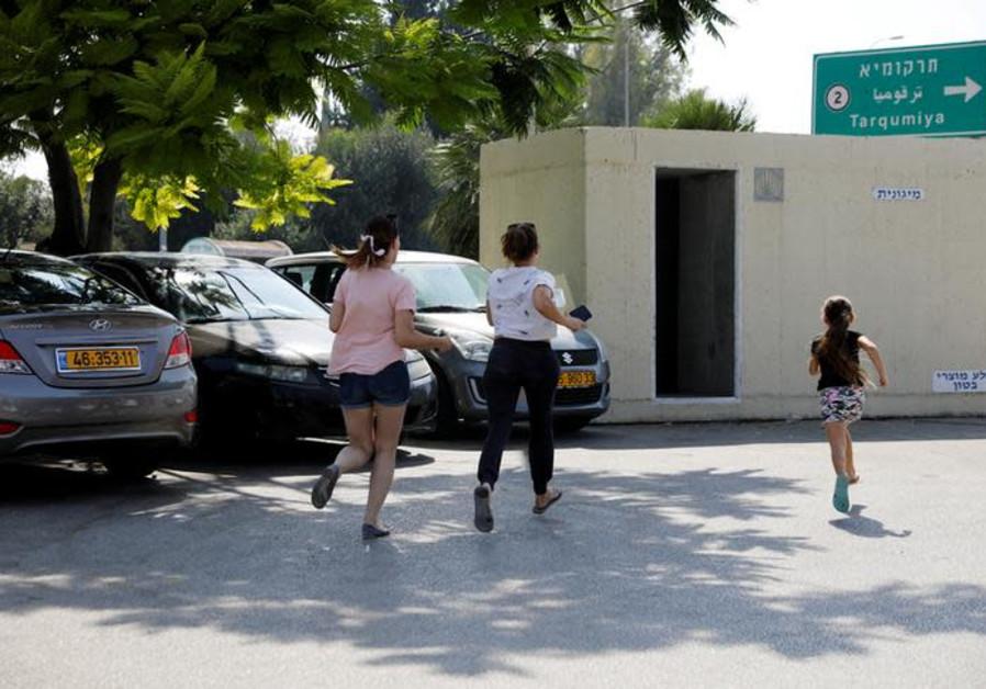 Israelis run for shelter as a siren sounds during a rocket attack near Yad Mordechai