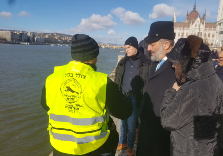 Deri, escorted by ZAKA divers, is standing at the banks of the Danube in Hungary
