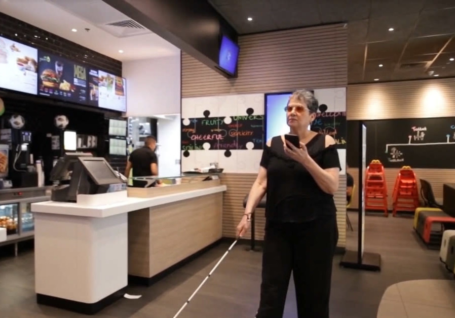 A visually impaired woman enters a McDonald's chain restaurant, 2019.