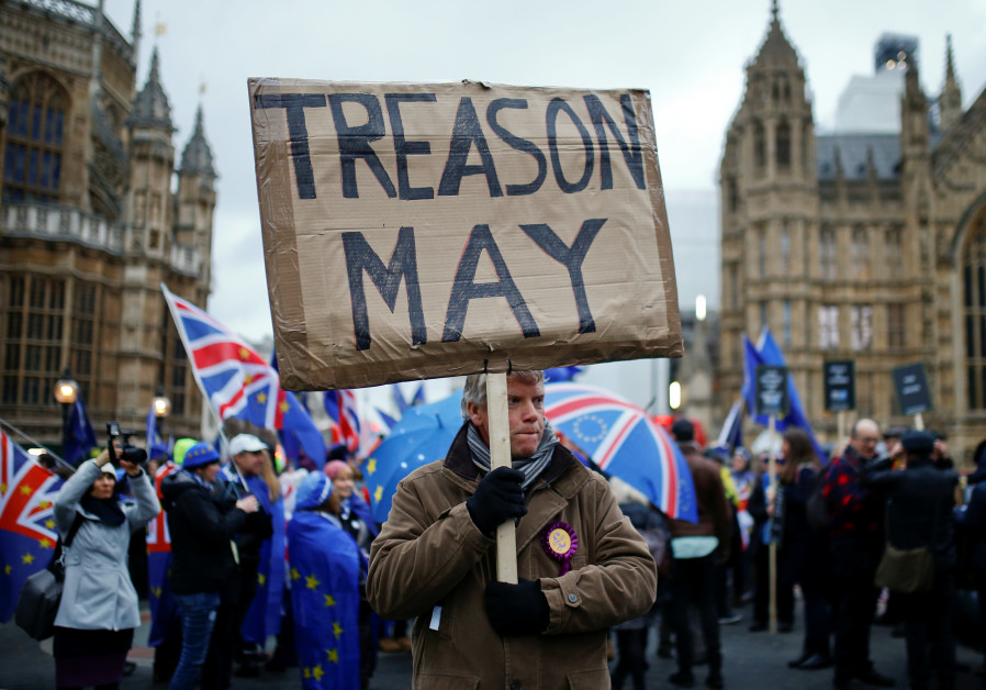 A pro-Brexit protester holds a banner as anti-Brexit protesters demonstrate outside the Houses of Pa