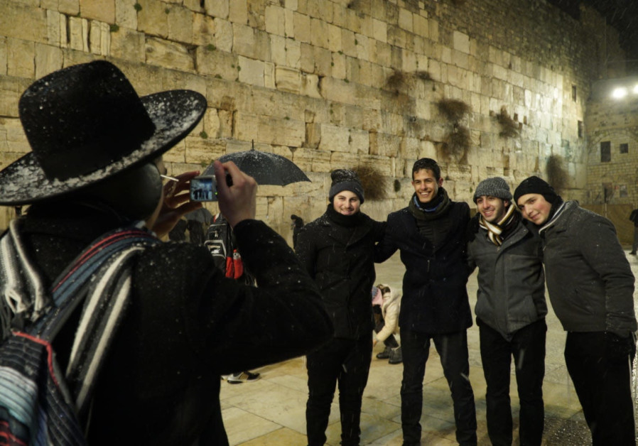 An orthodox Jew takes pictures of tourists at the Western Wall