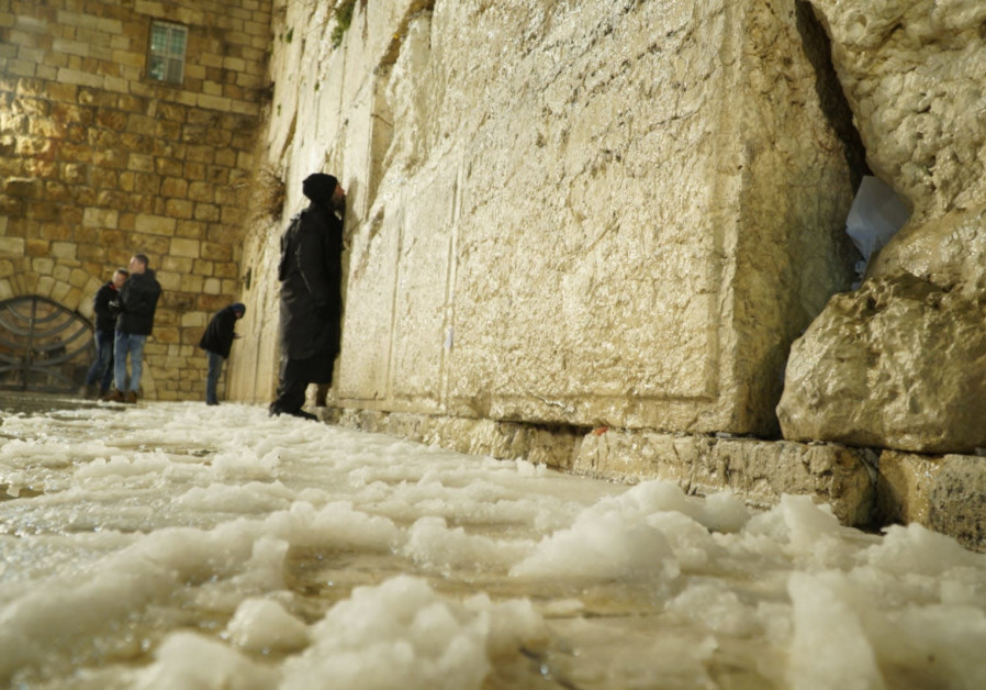 A note left in the cracks of the Western Wall; a few worshippers braved the cold to pray there.