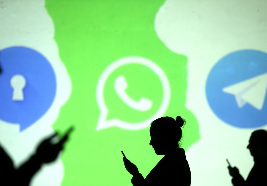 Silhouettes of mobile users next to the Whatsapp logo, March 28, 2018.
