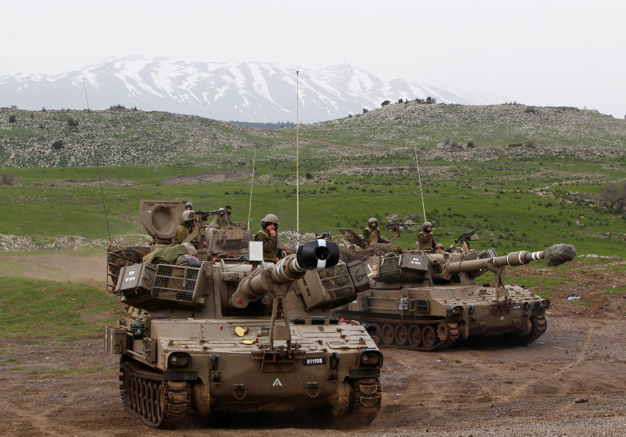 Mount Hermon is seen in the background as Israeli soldiers travel on mobile artillery units after an