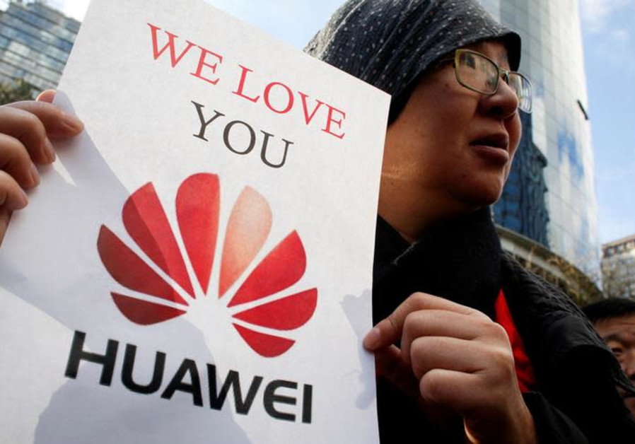 a visitor from China, holds a sign in support of Huawei CFO Meng Wanzhou