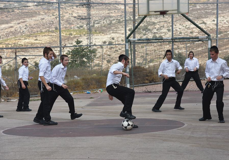 Haredi youngsters play soccer. Work and army are now increasingly viable options to complement studies. (Courtesy)