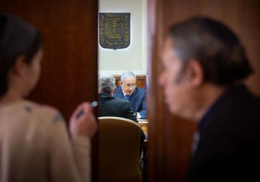 Prime Minister Benjamin Netanyahu is seen through an open door as he convenes a recent cabinet meeti