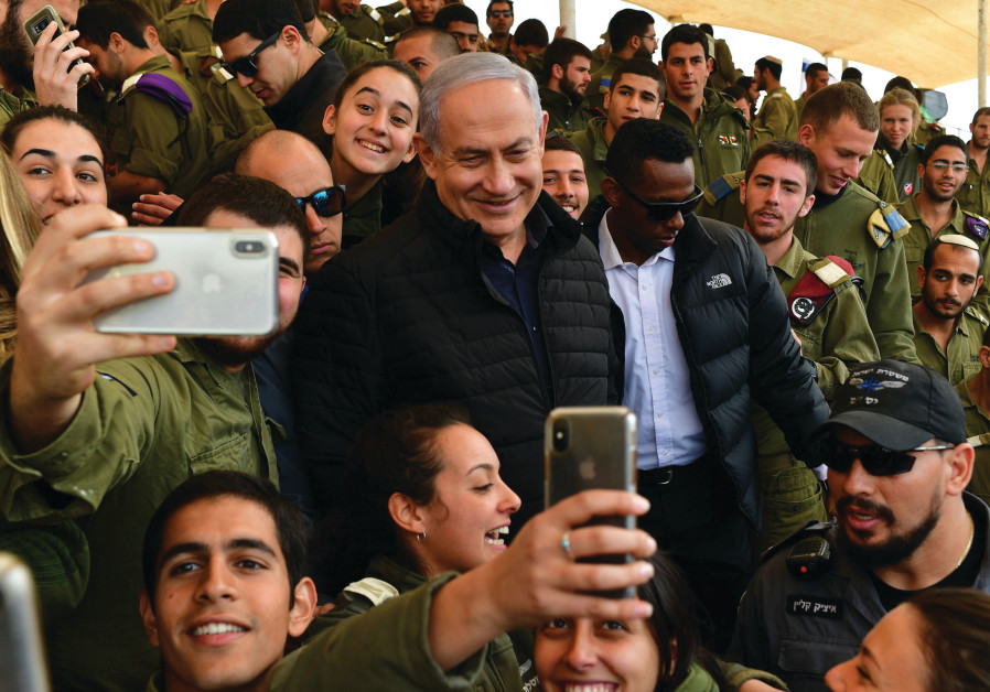 PRIME MINISTER Benjamin Netanyahu poses for selfies with soldiers at the Shizafon military base
