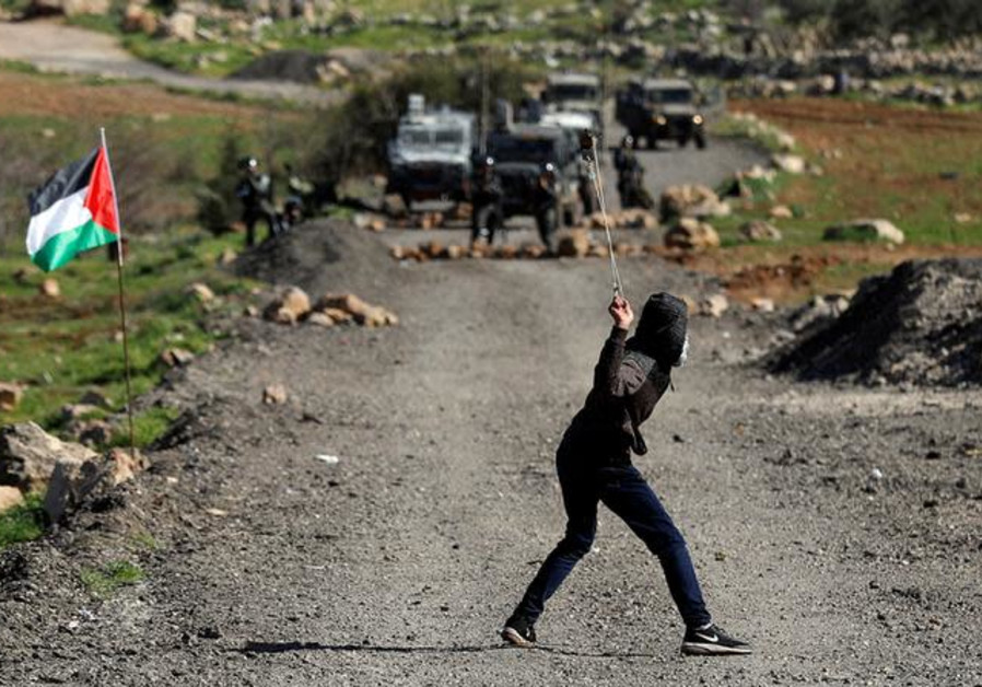 A Palestinian demonstrator uses a sling to hurl stones at Israeli troops during clashes at a protest