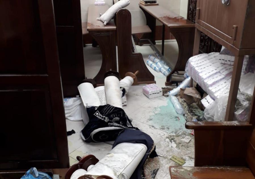 Torah scrolls strewn across the floor after the vandalism of a Jerusalem synagogue