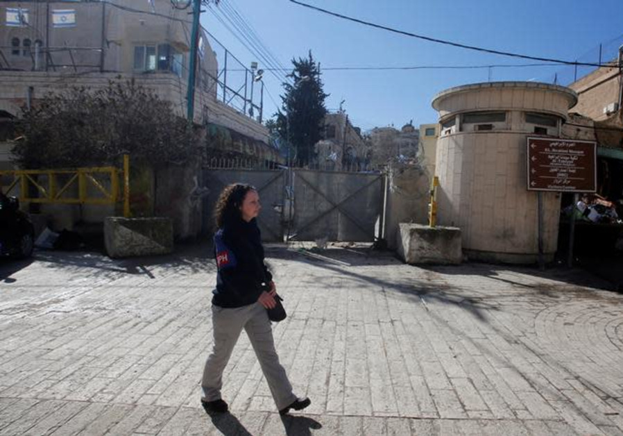 A member of the Temporary International Presence in Hebron (TIPH) walks past the Beit Romano