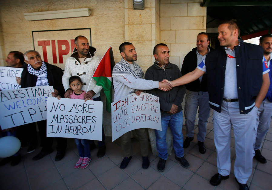 A Palestinian man shakes hands with a member of the Temporary International Presence in Hebron, TIPH