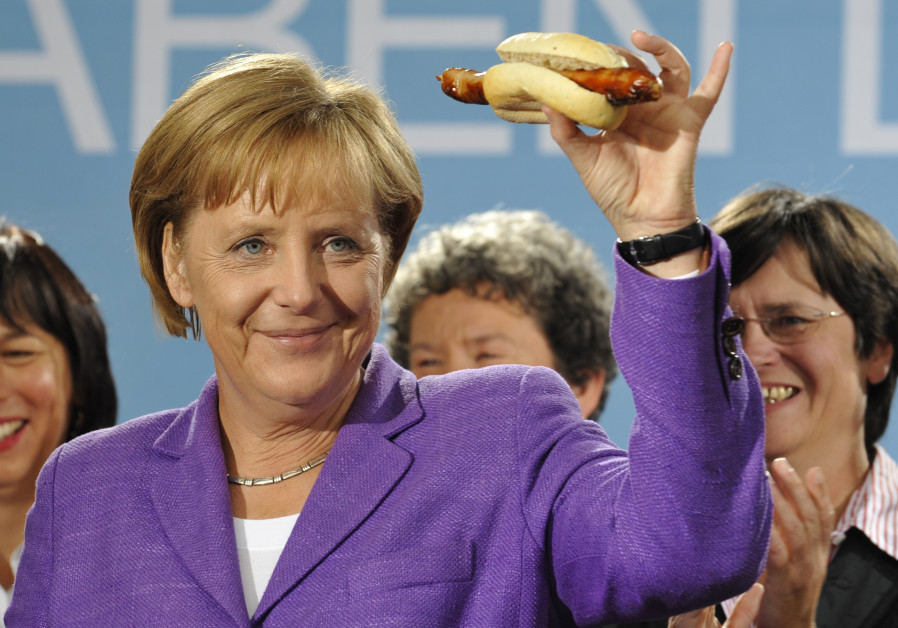German Chancellor Angela Merkel holds up a traditional Thuringia sausage in Erfurt
