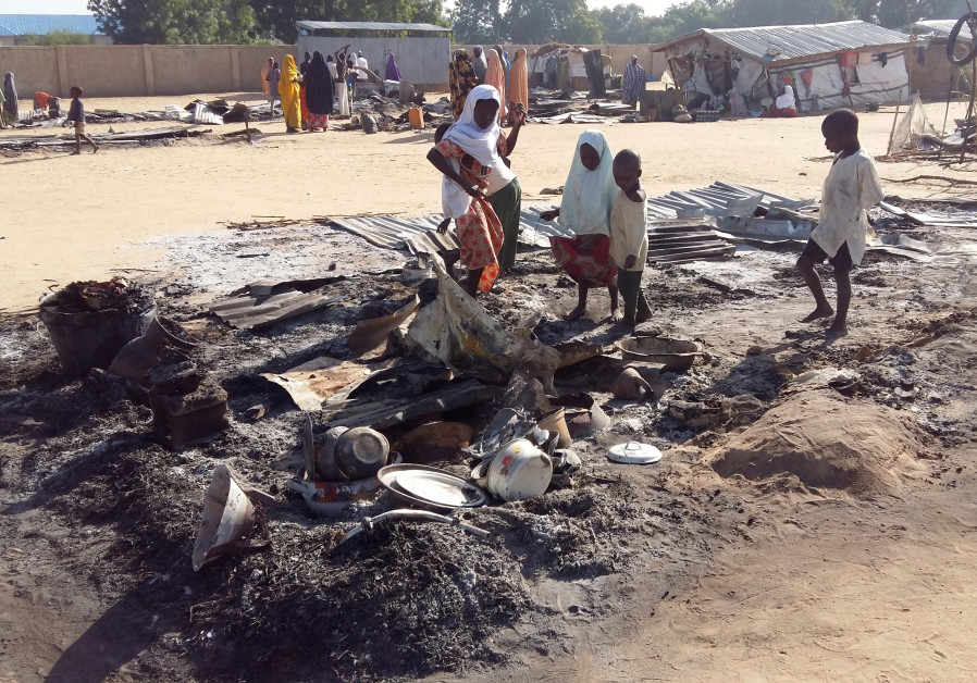 FILE PHOTO: People stand amid the damage at a camp for displaced people after a Boko Haram attack