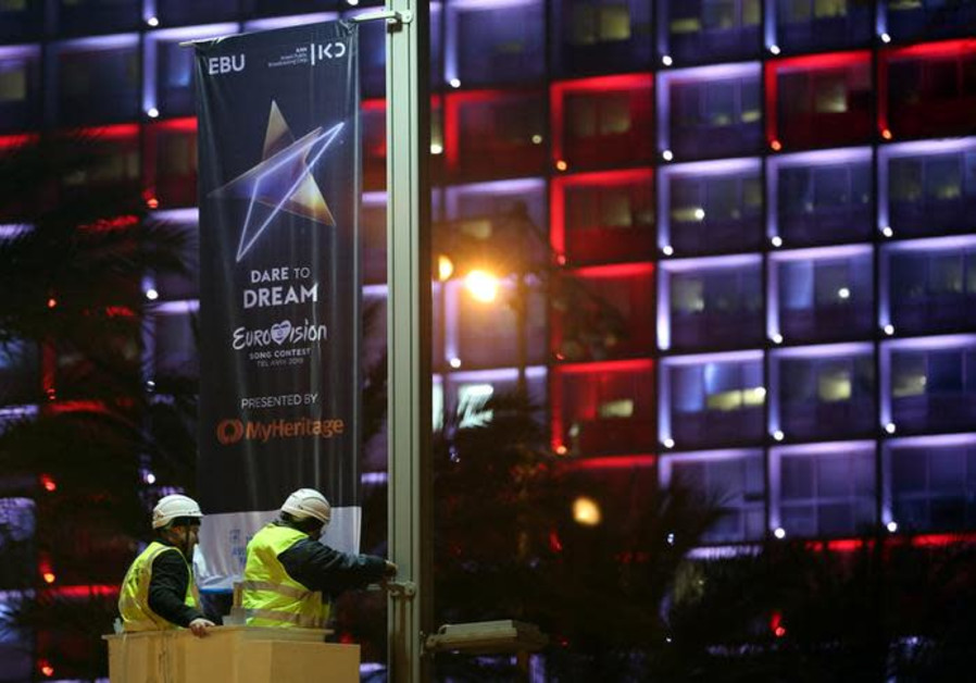 Labourers stand on a crane as they hang 2019 Eurovision Song Contest banners in Tel Aviv