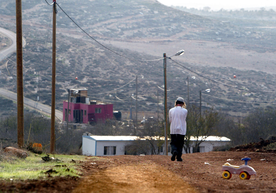 A Jewish settler walks at the Jewish settlement outpost of Adei Ad B in the West Bank