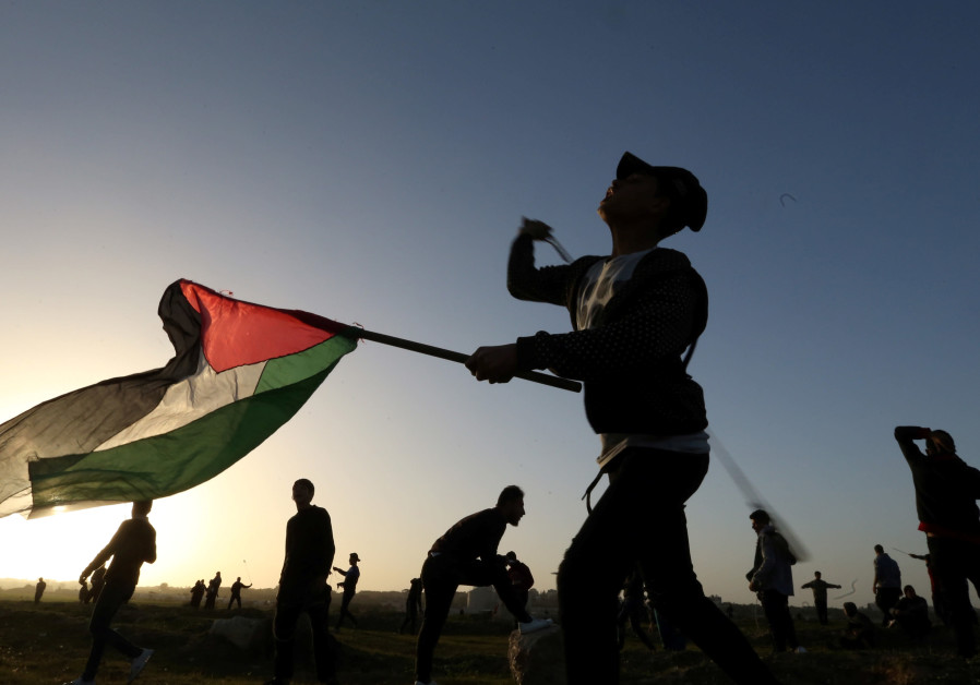 A demonstrator holding a Palestinian flag uses a sling to hurl stones at Israeli troops