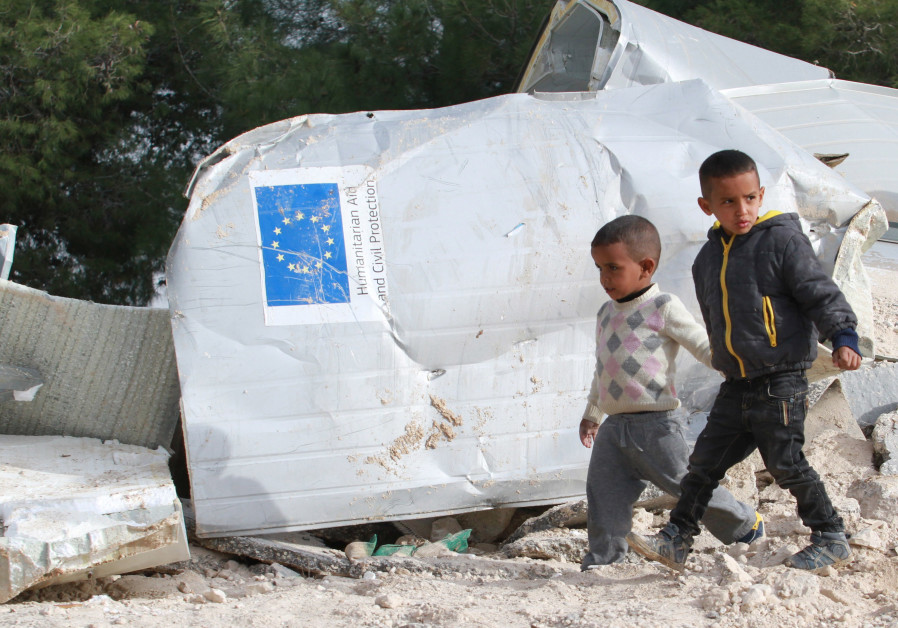 Palestinian boys walks past the remains of their family's dwelling, that was funded by the EU's huma