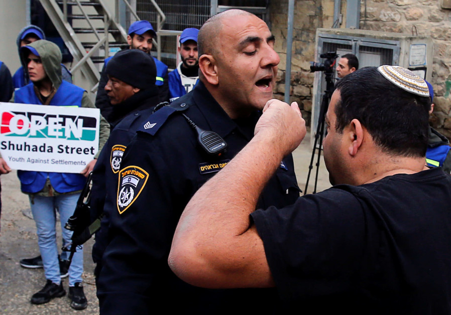 A Jewish settler argues with an Israeli policeman during a protest by Palestinians in Hebron, 2019.