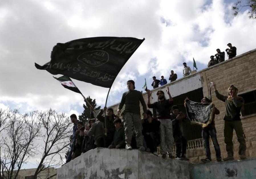 Les manifestants portent les drapeaux d'Al-Qaïda lors d'une manifestation antigouvernementale après les prières du vendredi