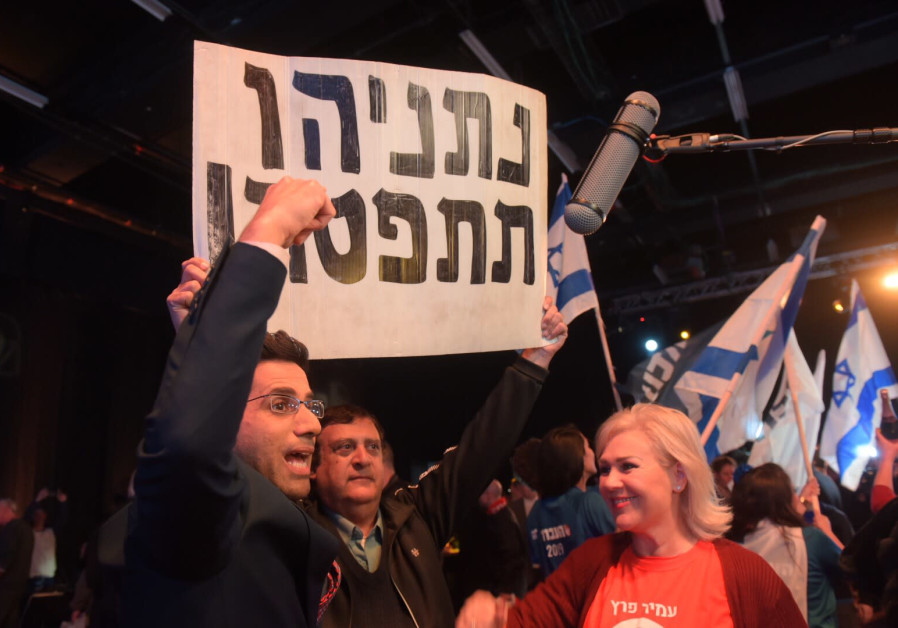 """A Labor party member holds a sign reading """"Netanyahu resign"""" outside the Tel Aviv Convention Center where Labor primaries were held Monday."""