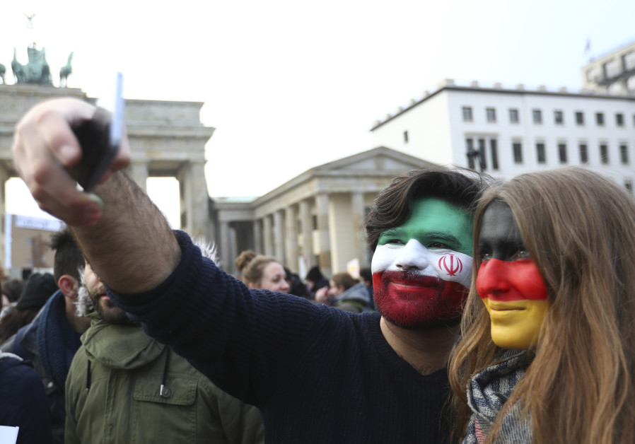 A couple, with their faces painted in the colours of Iranian and German national flags