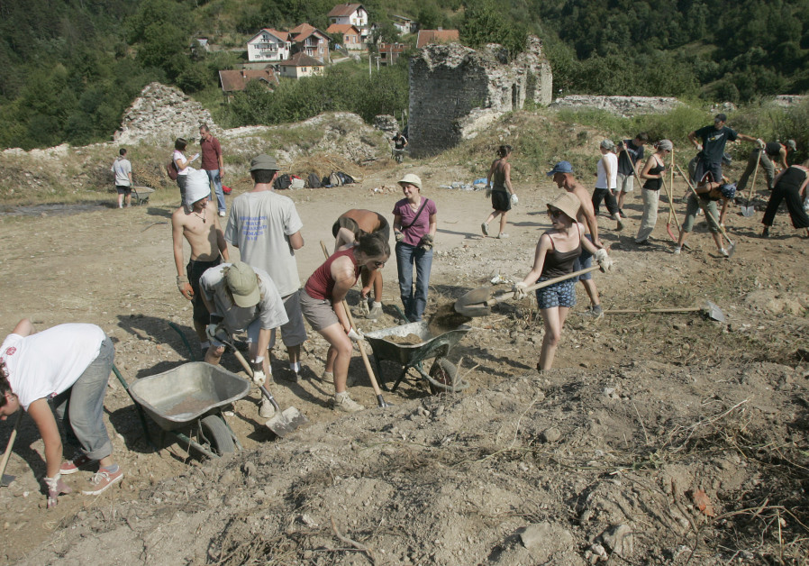 "Young volunteers clear earth from a medieval fortress above Srebrenica, Bosnia, as ""voluntourists."""
